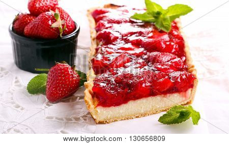 Strawberry jelly topping cheesecake tart on table