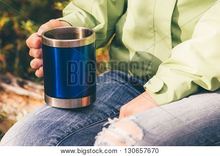 Touristic tea thermal cup in woman hand Travel Lifestyle concept vacations outdoor picnic in forest