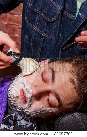 Shaving with a straight razor.The master is working on a way the client.