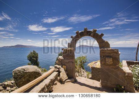 arch above titicaca lake in peru with blue sky