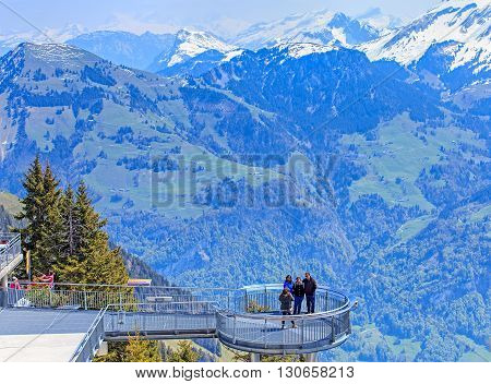 Mt. Stanserhorn, Switzerland - 7 May, 2016: view on the Alps with people posing for a photographer in the foreground. Stanserhorn is a mountain in Switzerland, located in the canton of Nidwalden near to the border with Obwalden.