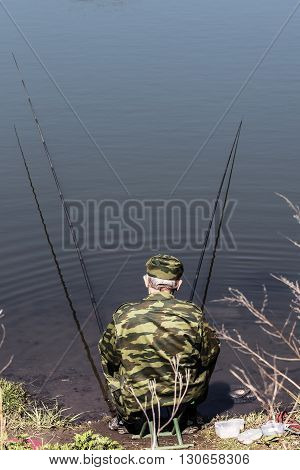 fisherman sits on the shore and catches a fish with two rods