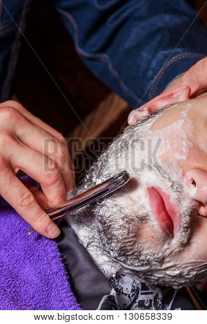 Shaving with a straight razor. The master is working on a way the client.