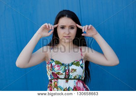 Brunette teenage girl with a blue background wall and headache