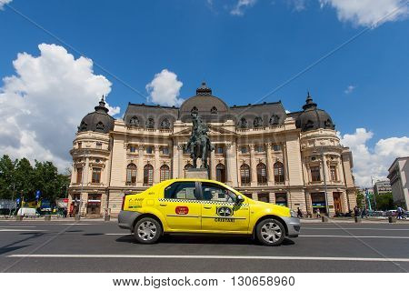 Bucharest, Romania, May 7, 2016: Central University Library and King Carol's statue in Bucharest with local yellow taxi passing by