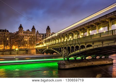 Paris Bir-Hakeim bridge at twilight with clouds and light trails of boats on the Seine River. The bridge also known as Passerelle de Passy is located in the 16th Arrondissement of Paris