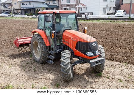 NAGOYA JAPAN - April 16, 2016: Farmer in tractor preparing land for sowing. Farmer in tractor preparing land with seedbed cultivator on April 16, 2016.