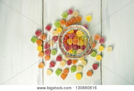 A glass container with vibrant gum drops with more candies on a light wooden texture beside it with copyspace
