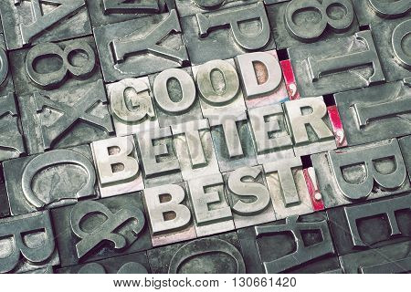 goodbetterbest exclamation made from metallic letterpress blocks with dark letters background