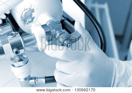 Hand on the oxygen cylinder valve in monochrome.