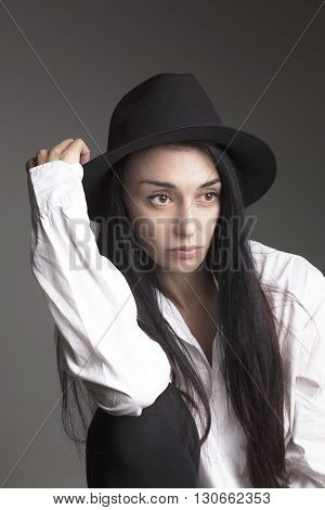 Stylish brunette  girl in light white shirt in a hat