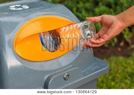 Man Putting Empty Plastic Bottle Into Public Recycling Bin.