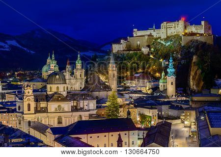 Night view of Salzburg old town with spires and Hohensalzburg Fortress.
