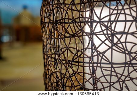 Lamp with white lighting accented by a shade that is made of small gauge dried twisted cane. Some dust particles can be seen trapped in the cane structure.