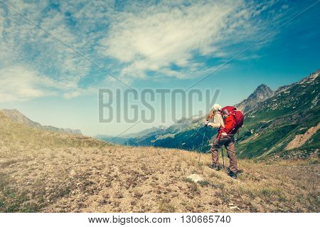 Woman with backpack mountaineering Travel Lifestyle concept active vacations outdoor mountains and clouds on background