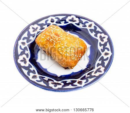 Traditional uzbek samsa bun with minced veal. Served on authentic oriental plate. Isolated on a white background.