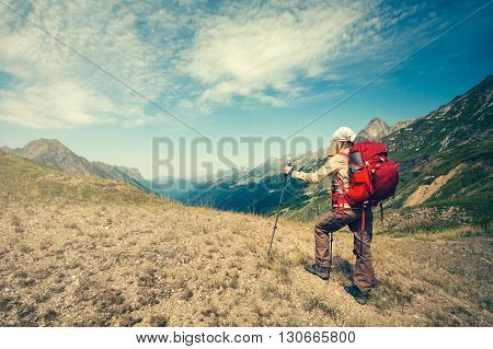 Traveler girl with red backpack hiking Travel Lifestyle concept active vacations outdoor mountains and clouds on background