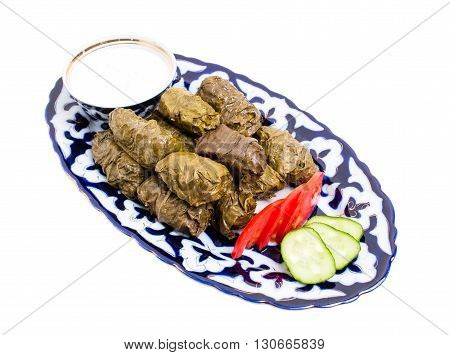 Traditional eastern appetizer dolma stuffed with rice and meat. Served with sour cream sauce and fresh vegetables. Isolated on a white background.