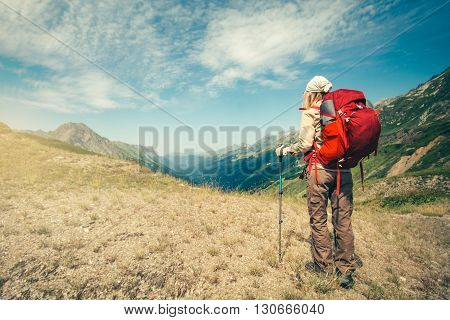 Woman Traveler with red backpack mountaineering Travel Lifestyle concept vacations outdoor mountains and clouds on background