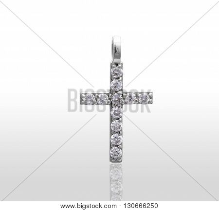 Gold pendant in the shape of a cross with diamonds. Isolated white background.