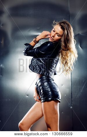 Beautiful woman in black leather jacket and shorts