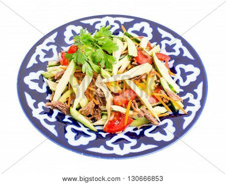 Delicious veal salad with cucumbers and avocado on authentic oriental plate. Isolated on a white background.