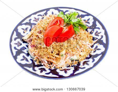 Delicious veal salad with fresh vegetables covered with grated walnuts on authentic oriental plate. Isolated on a white background.