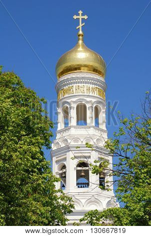 Beautiful russian orthodox cathedral with gold dome and white bell tower on blue sky background.