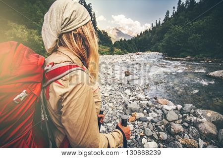 Woman Traveler with backpack hiking Travel Lifestyle concept active vacations outdoor river and mountains wild nature on background