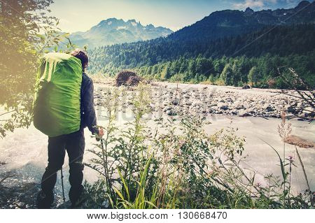 Man with backpack hiking Travel Lifestyle concept river and mountains on background adventure vacations outdoor