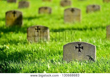 Gravestone of a unknown german soldier with the iron cross symbol in a heroes graveyard