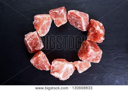 Himalayan pink crystal salt on dark background.