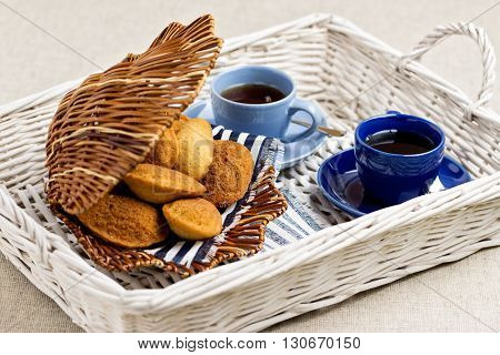 Breakfast. French pastries madeleines with cup of coffee. Selective focus.