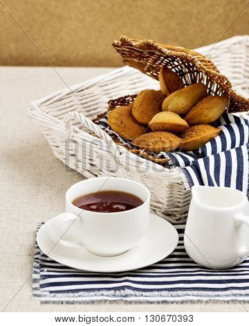 Breakfast. French pastries madeleines with cup of tea. Selective focus.
