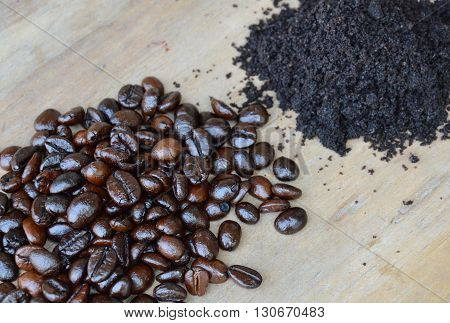 dark roast coffee bean and powder on wooden board