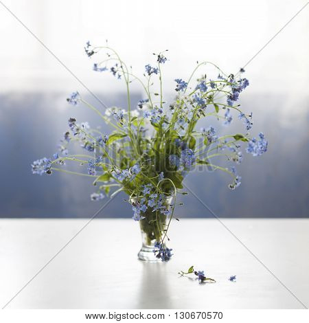 Forget-me-not blue forest flowers bouquet on table