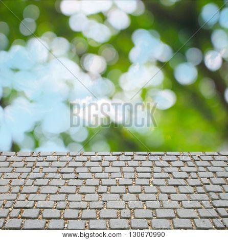 bokeh blur from natural tree for texture background and cobble stone street