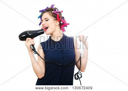 Female vocalist in curler uses hairdryer like microphone. Isolated.