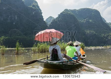Tourists riding on boat whilst the trip to Tam Coc caves in Hoa Lu capital located in Ninh Binh, Vietam. On the background limestone karst mountains are seen covered by lush greeneries.