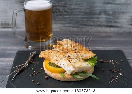 Grilled fish with onion and pepper on the bread and mug of beer.