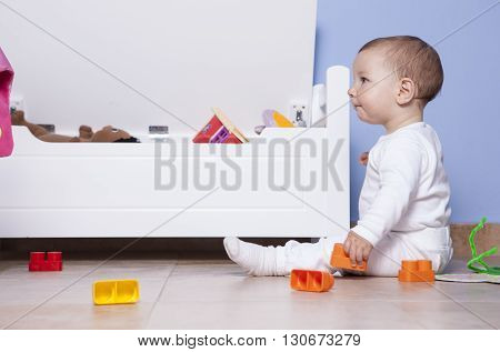 9 month baby boy playing with in his toy room