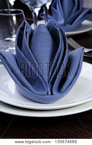Folded textile cloth in the form of flower bud on a plate