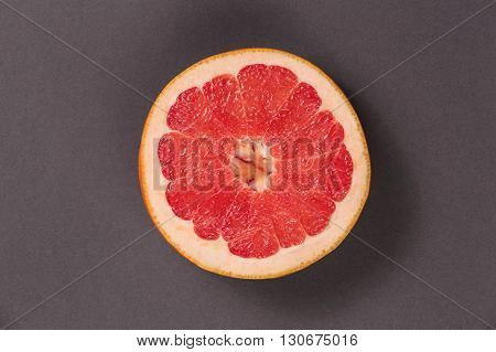 Top view fresh fruit, fruit for diet, food and objects concept. Close up of ripe grapefruit slice on grey recycled cardboard texture. Ripe juicy fruit. Juicy poster with grapefruit.