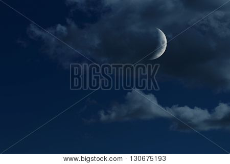 young growing moon in night sky with clouds, no stars