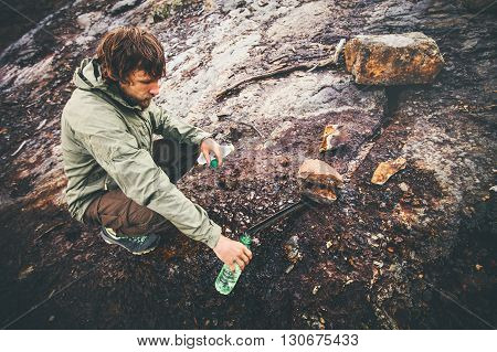 Man Traveler taking mineral water in bottle from natural well rusty rocks on background Lifestyle Travel survival concept