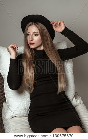 Woman with long straight blond hair in a black hat and dress sitting on a chair. Beauty portrait of model with perfect make up and red lips