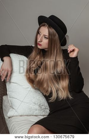 Woman with long wavy blond hair in a black hat and dress sitting on a chair. Beauty portrait of model with chic evening make up and red lips