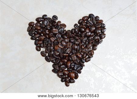 coffee bean arrange in heart shape on tile