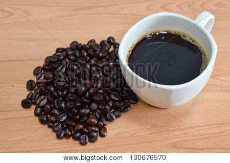black coffee cup and seed on desk