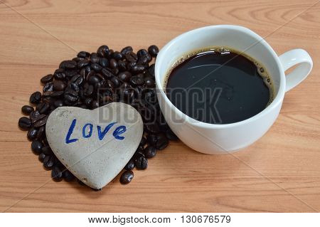 black coffee cup and bean with heart stone